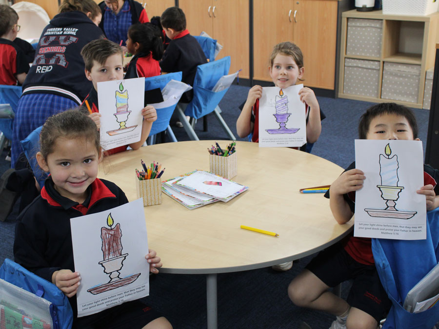Reception students holding images