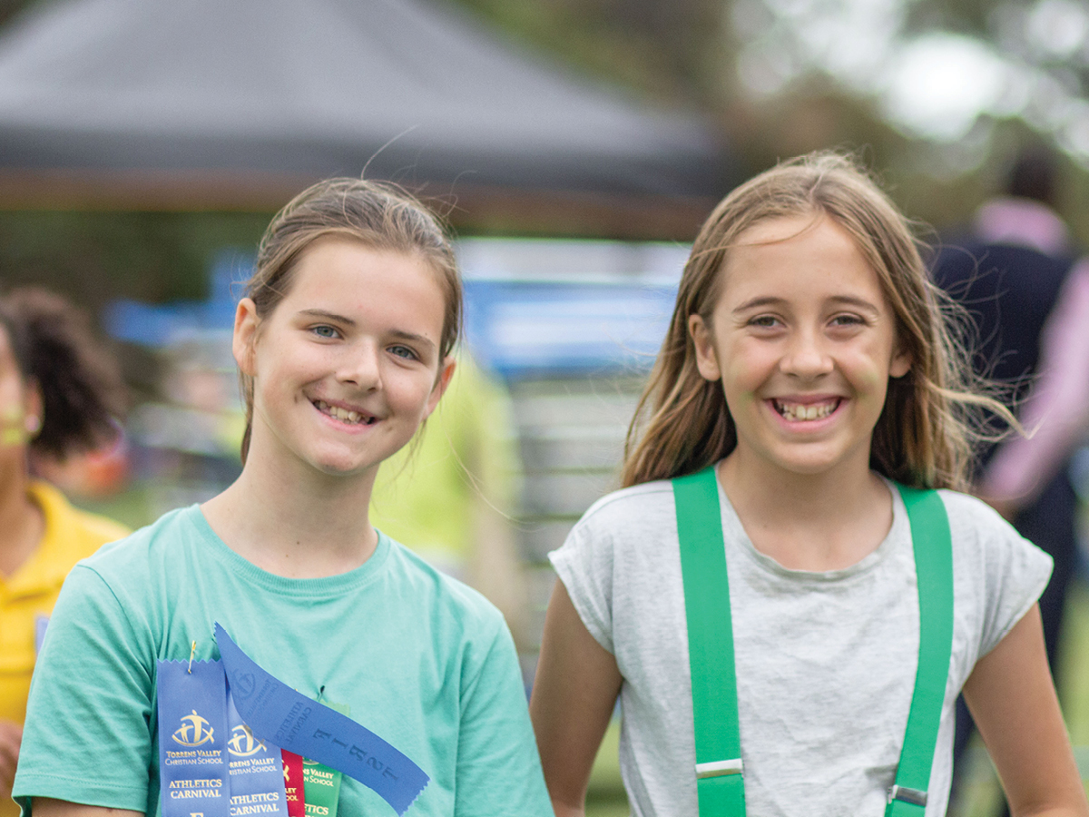 Two young teens smiling in their sports gear